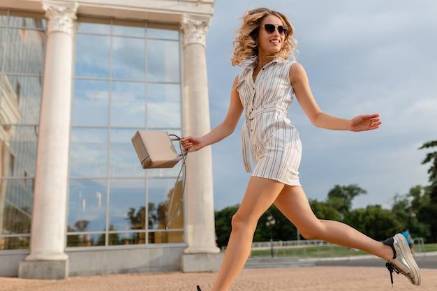Młoda atrakcyjna stylowa kobieta bieganie, skoki śmieszne w trampki na ulicy miasta w białej sukni w stylu letniej mody na sobie okulary przeciwsłoneczne i torebkę