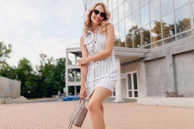 Młoda atrakcyjna stylowa kobieta o blond włosach spaceru na ulicy miasta w białej sukni stylu letniej mody na sobie okulary przeciwsłoneczne
