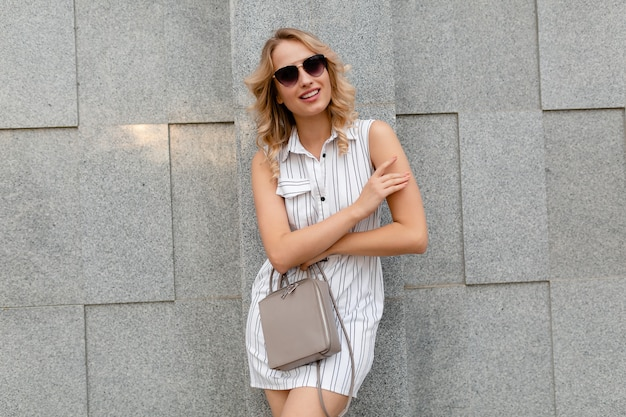 Młoda atrakcyjna stylowa kobieta z blond kręcone fryzury spaceru na ulicy miasta w lato moda styl biała sukienka w paski na sobie okulary przeciwsłoneczne trzymając torebkę