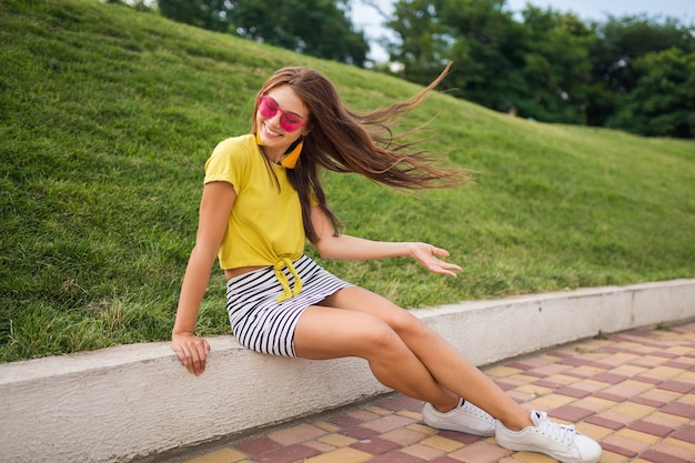 Młoda atrakcyjna stylowa uśmiechnięta kobieta bawiąca się w parku miejskim, pozytywna, emocjonalna, ubrana w żółty top, mini spódniczka w paski, różowe okulary przeciwsłoneczne, białe trampki, trend w modzie lato, długie nogi