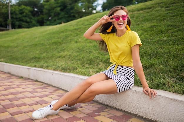 Młoda atrakcyjna stylowa uśmiechnięta kobieta bawiąca się w parku miejskim, pozytywna, emocjonalna, ubrana w żółty top, mini spódniczka w paski, różowe okulary przeciwsłoneczne, białe trampki, trend w modzie na lato, znak pokoju