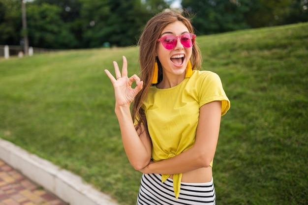 Młoda atrakcyjna stylowa uśmiechnięta kobieta bawiąca się w parku miejskim, pozytywna, emocjonalna, ubrana w żółty top, mini spódniczka w paski, różowe okulary przeciwsłoneczne, trend w modzie w stylu letnim, pokazujący znak dobra, kolorowy