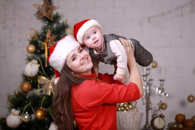 Młoda atrakcyjna szczęśliwa matka w czapce mikołaja miło spędza czas z synem w domu w pobliżu choinki. rodzina, szczęście, wakacje, koncepcja nowego roku