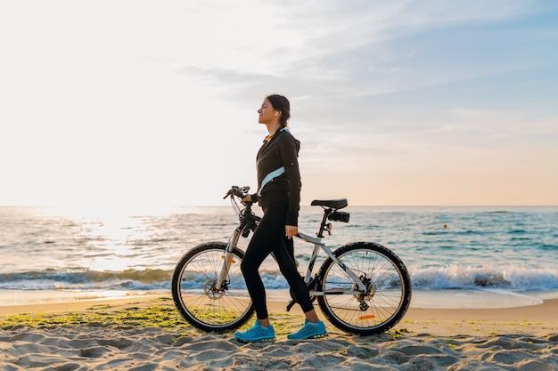 Młoda atrakcyjna szczupła kobieta jedzie na rowerze, sport na plaży o poranku wschód słońca w sportowej fitness sportowej odzieży, aktywny zdrowy tryb życia, uśmiechnięta szczęśliwa zabawa
