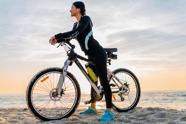 Młoda atrakcyjna szczupła kobieta jedzie na rowerze, sport w porannym wschodzie słońca letniej plaży w sportowej odzieży fitness, aktywny zdrowy tryb życia, uśmiechnięta szczęśliwa zabawa