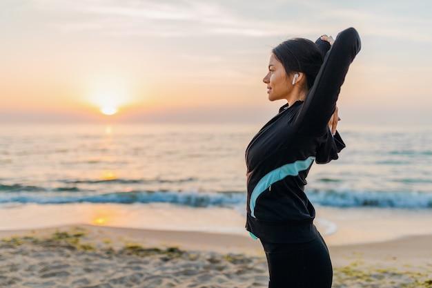 Młoda atrakcyjna szczupła kobieta robi ćwiczenia sportowe na plaży o poranku wschód słońca w strojach sportowych, zdrowy styl życia, słuchanie muzyki na słuchawkach, rozciąganie
