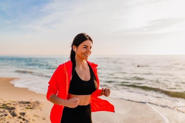 Młoda atrakcyjna szczupła kobieta robi ćwiczenia sportowe w porannym joggingu o wschodzie słońca na plaży w odzieży sportowej, zdrowym stylu życia, słuchaniu muzyki na słuchawkach, na sobie różową wiatrówkę