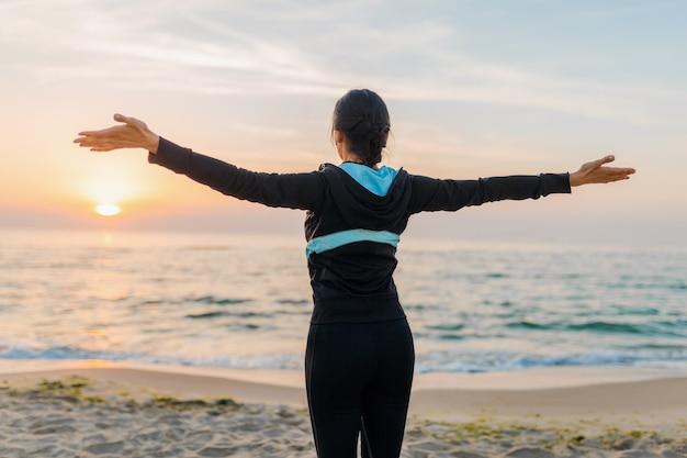 Młoda atrakcyjna szczupła kobieta wita słońce ciew z tyłu trzymając się za ręce, robi ćwiczenia sportowe na plaży o poranku wschód słońca w odzieży sportowej, zdrowym stylu życia