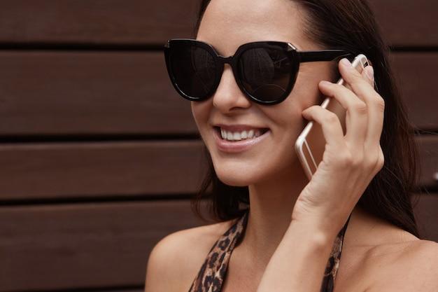 Młoda atrakcyjna turystka rozmawia przez telefon komórkowy, nosi okulary przeciwsłoneczne i kostium kąpielowy z lampartami, uśmiecha się i wygląda na szczęśliwą