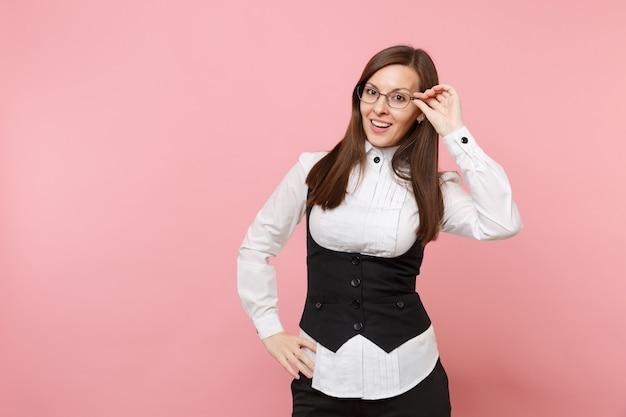 Młoda atrakcyjna udanego biznesu kobieta w czarnym garniturze, białej koszuli, trzymając okulary na białym tle na pastelowym różowym tle. szefowa. koncepcja bogactwa kariery osiągnięcia. skopiuj miejsce na reklamę.