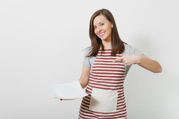Młoda atrakcyjna uśmiechnięta brunetka kaukaski gospodyni w pasiasty fartuch, szary t-shirt na białym tle. piękna gospodyni kobieta trzyma biały pusty talerz