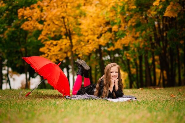 Młoda atrakcyjna uśmiechnięta dziewczyna pod parasolem w lesie jesienią