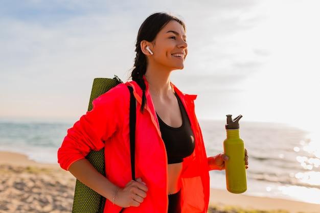 Młoda atrakcyjna uśmiechnięta kobieta uprawia sport o porannym wschodzie słońca na plaży morskiej trzymając matę do jogi i butelkę wody, zdrowy styl życia, słuchanie muzyki na słuchawkach, na sobie różową wiatrówkę