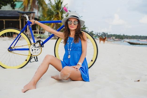 Młoda atrakcyjna uśmiechnięta kobieta w niebieskiej sukience siedzi na piasku na tropikalnej plaży z rowerem na sobie kapelusz i okulary przeciwsłoneczne