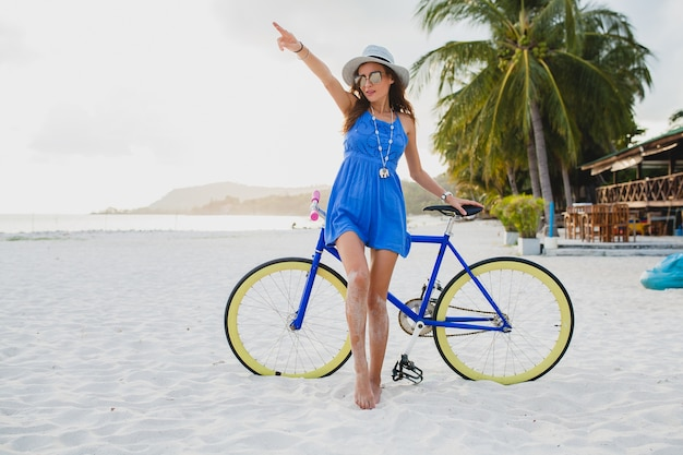 Młoda atrakcyjna uśmiechnięta kobieta w niebieskiej sukience spaceru na tropikalnej plaży z rowerem na sobie kapelusz i okulary przeciwsłoneczne