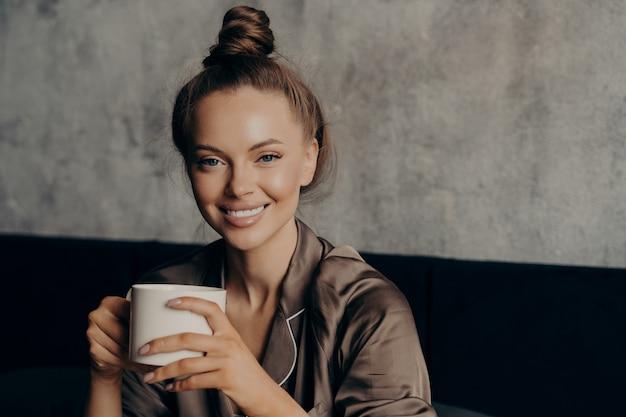 Młoda atrakcyjna wesoła kobieta z pięknym szerokim uśmiechem trzymająca poranną filiżankę kawy i uśmiechająca się do kamery, siedząc w sypialni w nowoczesnym apartmnecie po przebudzeniu, nosi satynową brązową piżamę