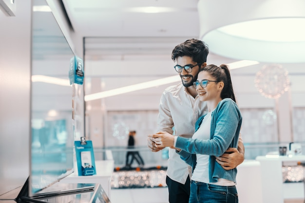 Młoda atrakcyjna, wielokulturowa para wypróbowuje nowy telewizor plazmowy, który chce kupić. wnętrze sklepu technicznego.