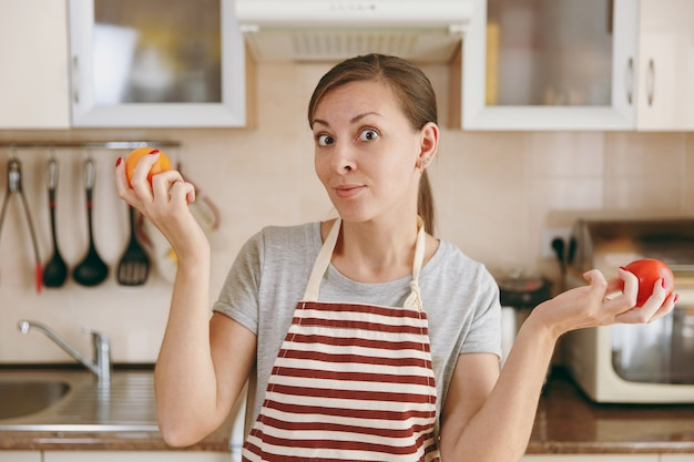Młoda atrakcyjna, zamyślona kobieta w fartuchu postanawia wybrać w kuchni pomidora w kolorze czerwonym lub żółtym. koncepcja diety. zdrowy tryb życia. gotowanie w domu. przygotuj jedzenie.