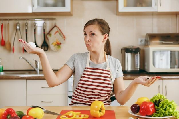 Młoda, atrakcyjna, zamyślona kobieta w fartuchu wybiera w kuchni między kurczakiem a jajkiem przepiórczym. koncepcja diety. zdrowy tryb życia. gotowanie w domu. przygotuj jedzenie.