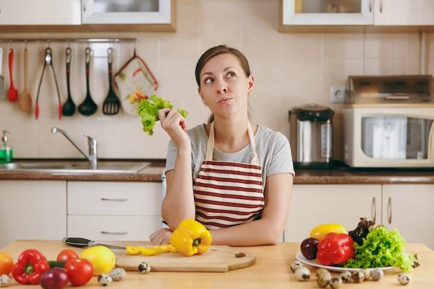 Młoda atrakcyjna zamyślona kobieta w fartuchu z liściem sałaty w kuchni. koncepcja diety. zdrowy tryb życia. gotowanie w domu. przygotuj jedzenie.