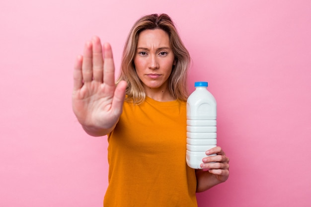 Młoda australijska kobieta trzyma butelkę mleka na białym tle na różowym tle stojącej z wyciągniętą ręką pokazując znak stopu, uniemożliwiając ci.