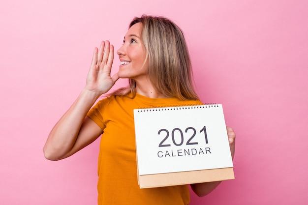 Młoda australijska kobieta trzyma kalendarz na białym tle na różowym tle krzycząc i trzymając dłoń w pobliżu otwartych ust.