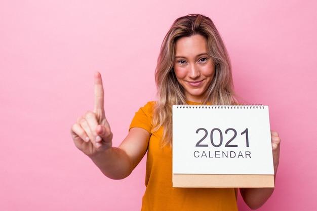 Młoda australijska kobieta trzyma kalendarz na białym tle na różowym tle pokazując numer jeden palcem.