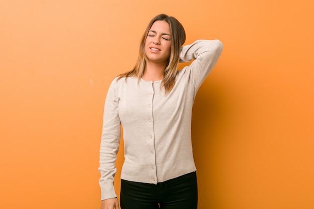 Młoda autentyczna charyzmatyczna kobieta o ścianę cierpiącą na ból szyi z powodu siedzącego trybu życia.