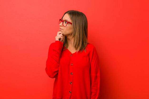 Młoda autentyczna charyzmatyczna kobieta o ścianę, która patrzy w bok z wątpliwym i sceptycznym wyrazem twarzy