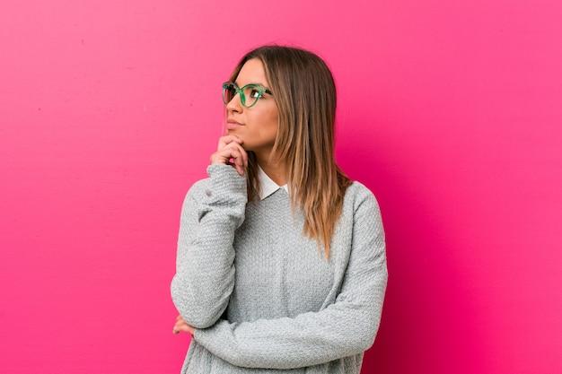 Młoda autentyczna charyzmatyczna prawdziwa kobieta, kobieta na ścianie, patrząca na boki z wyrazem wątpliwości i sceptycyzmu.