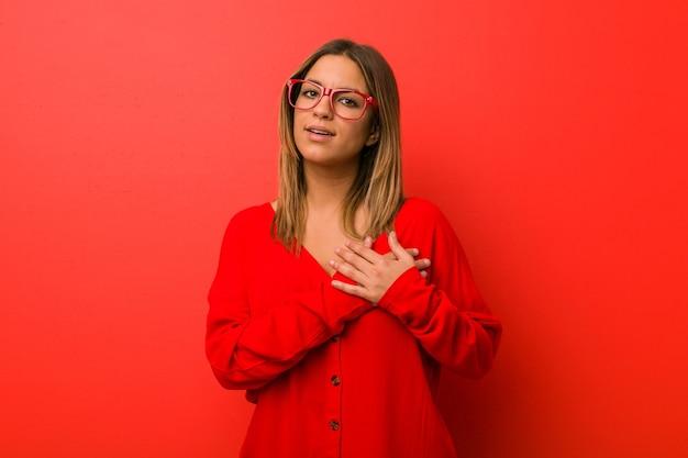 Młoda, autentyczna, charyzmatyczna, prawdziwa kobieta kobieta przy ścianie ma przyjazny wyraz, przyciskając dłoń do piersi. koncepcja miłości.