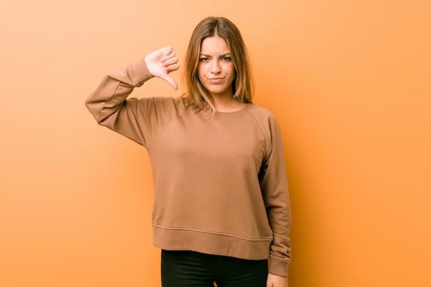 Młoda autentyczna charyzmatyczna prawdziwa kobieta, kobieta przy ścianie, pokazująca niechęć, kciuk w dół. pojęcie nieporozumienia.