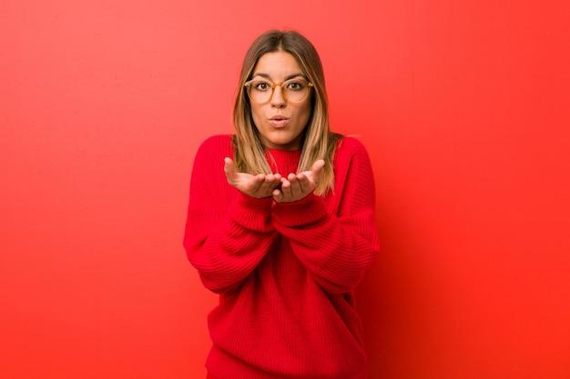 Młoda autentyczna charyzmatyczna prawdziwa kobieta, kobieta przy ścianie, składające usta i trzymające dłonie, by wysłać buziaka.