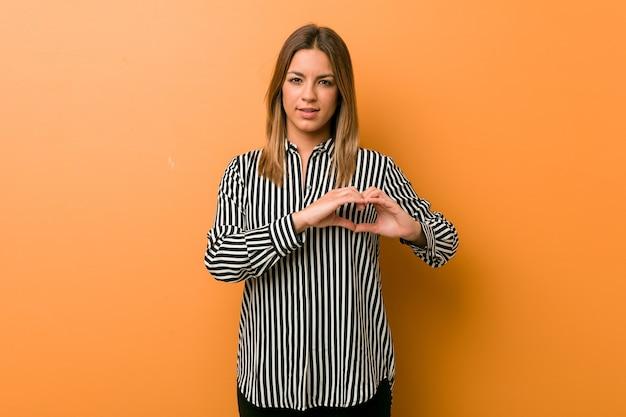 Młoda, autentyczna, charyzmatyczna prawdziwa kobieta kobieta przy ścianie, uśmiechnięta i pokazująca kształt serca z rękami.