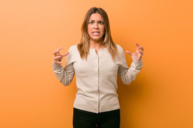 Młoda autentyczna charyzmatyczna prawdziwa kobieta o ścianę krzyczącą z wściekłości.
