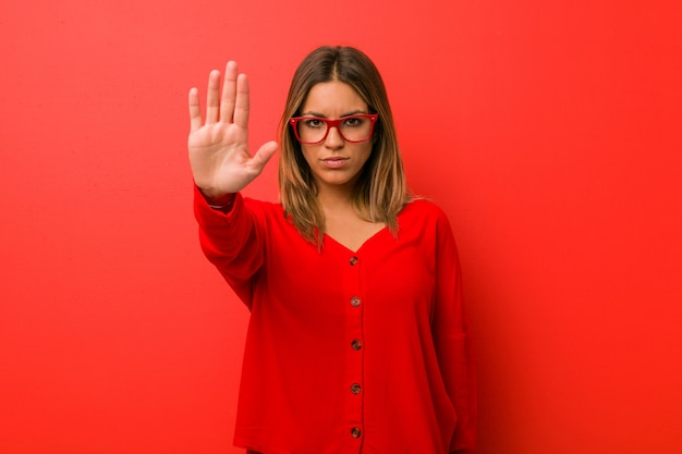 Młoda autentyczna charyzmatyczna prawdziwa kobieta o ścianę stojącą z wyciągniętą ręką pokazującą znak stopu, zapobiegającą ci.