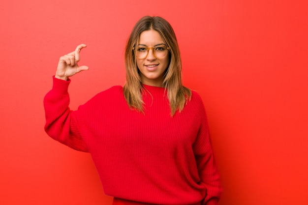 Młoda autentyczna charyzmatyczna prawdziwa kobieta o ścianę trzymająca coś z palcami wskazującymi, uśmiechnięta i pewna siebie.