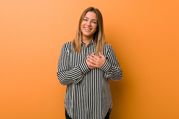 Młoda autentyczna charyzmatyczna prawdziwa kobieta przy ścianie ma przyjazny wyraz, przyciskając dłoń do piersi. koncepcja miłości.