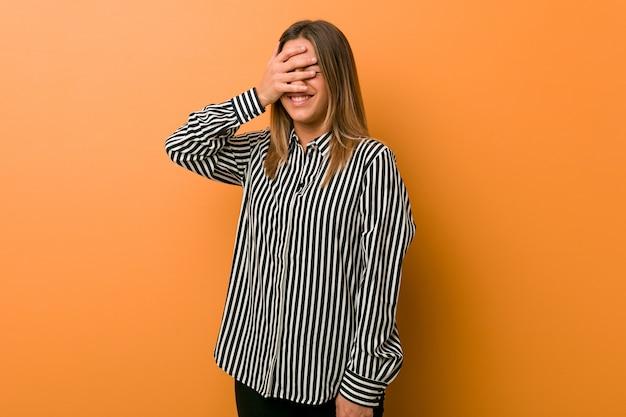 Młoda autentyczna charyzmatyczna prawdziwa kobieta przy ścianie mruga palcami do kamery, zakłopotana zakrywająca twarz.