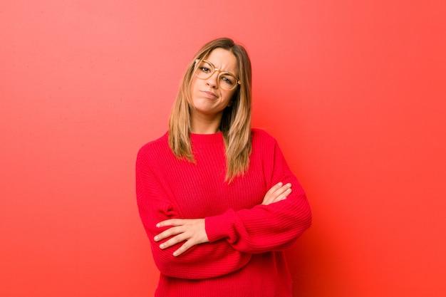 Młoda autentyczna charyzmatyczna prawdziwa kobieta przy ścianie niezadowolona patrząc w kamerę z sarkastyczną miną.