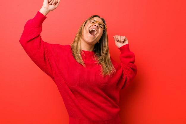 Młoda autentyczna charyzmatyczna prawdziwa kobieta przy ścianie świętuje wyjątkowy dzień, skacze i energicznie podnosi ręce.