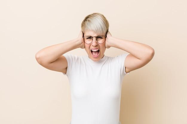 Młoda autentyczna naturalna kobieta ubrana w białą koszulę zakrywającą uszy rękami, starająca się nie słyszeć zbyt głośnego dźwięku.