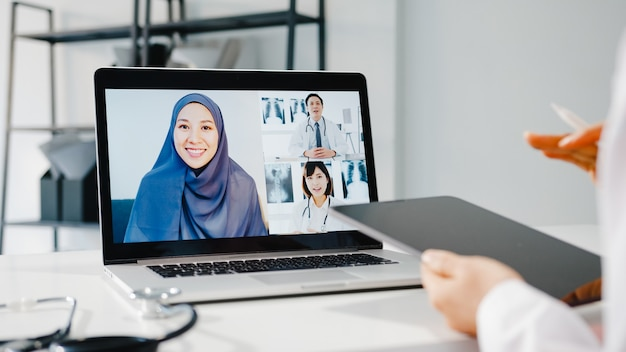 Młoda azja lekarka w białym mundurze medycznym ze stetoskopem za pomocą komputera laptop rozmawia wideokonferencję