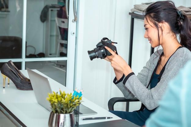Młoda azja piękna kobieta bierze fotografię i pracuje online e-commerce robić zakupy w odzieżowym sklepie.