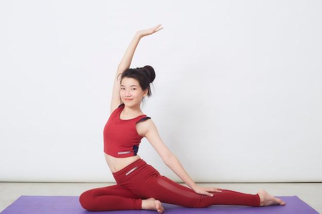 Młoda azjatka ćwiczy na jasnym tle