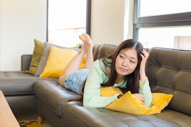 Młoda azjatka czuje się zdziwiona i zdezorientowana, drapiąc się po głowie i patrząc w bok