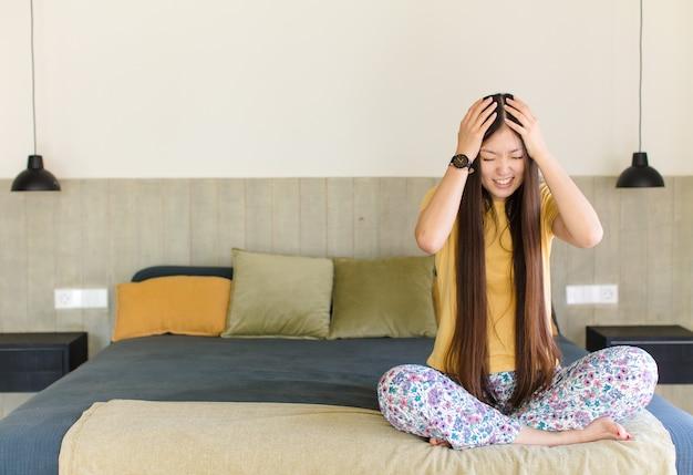 Młoda azjatka czuje się zestresowana i sfrustrowana, podnosi ręce do głowy, czuje się zmęczona, nieszczęśliwa i ma migrenę