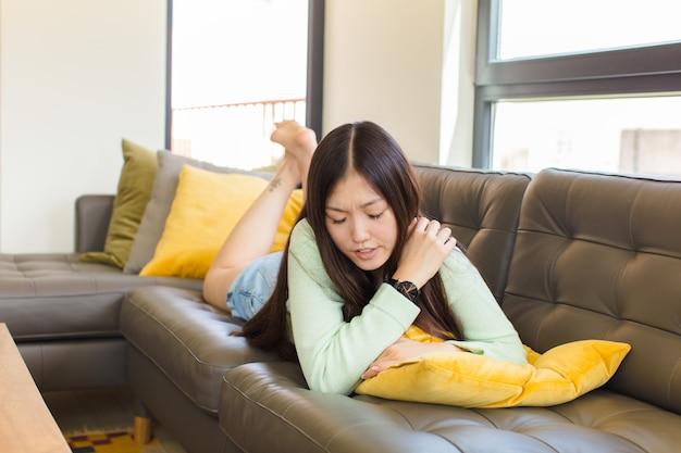 Młoda azjatka czuje się zmęczona, zestresowana, niespokojna, sfrustrowana i przygnębiona, cierpi na ból pleców lub szyi