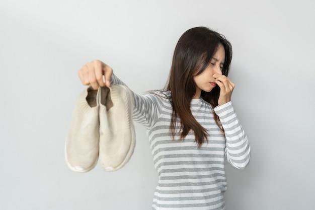 Młoda azjatka czuje się zniesmaczona zapachem butów po długim noszeniu. kobieta trzyma brudne śmierdzące buty. obuwie potrzebne do czyszczenia i usuwania nieprzyjemnych zapachów. nieprzyjemna koncepcja zapachu