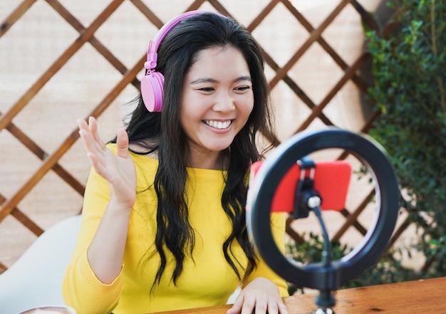Młoda azjatka gotująca na parze powitanie wideo ze społecznością dłoni - influencer z zestawem słuchawkowym, smartfonem i diodą led - technologia -